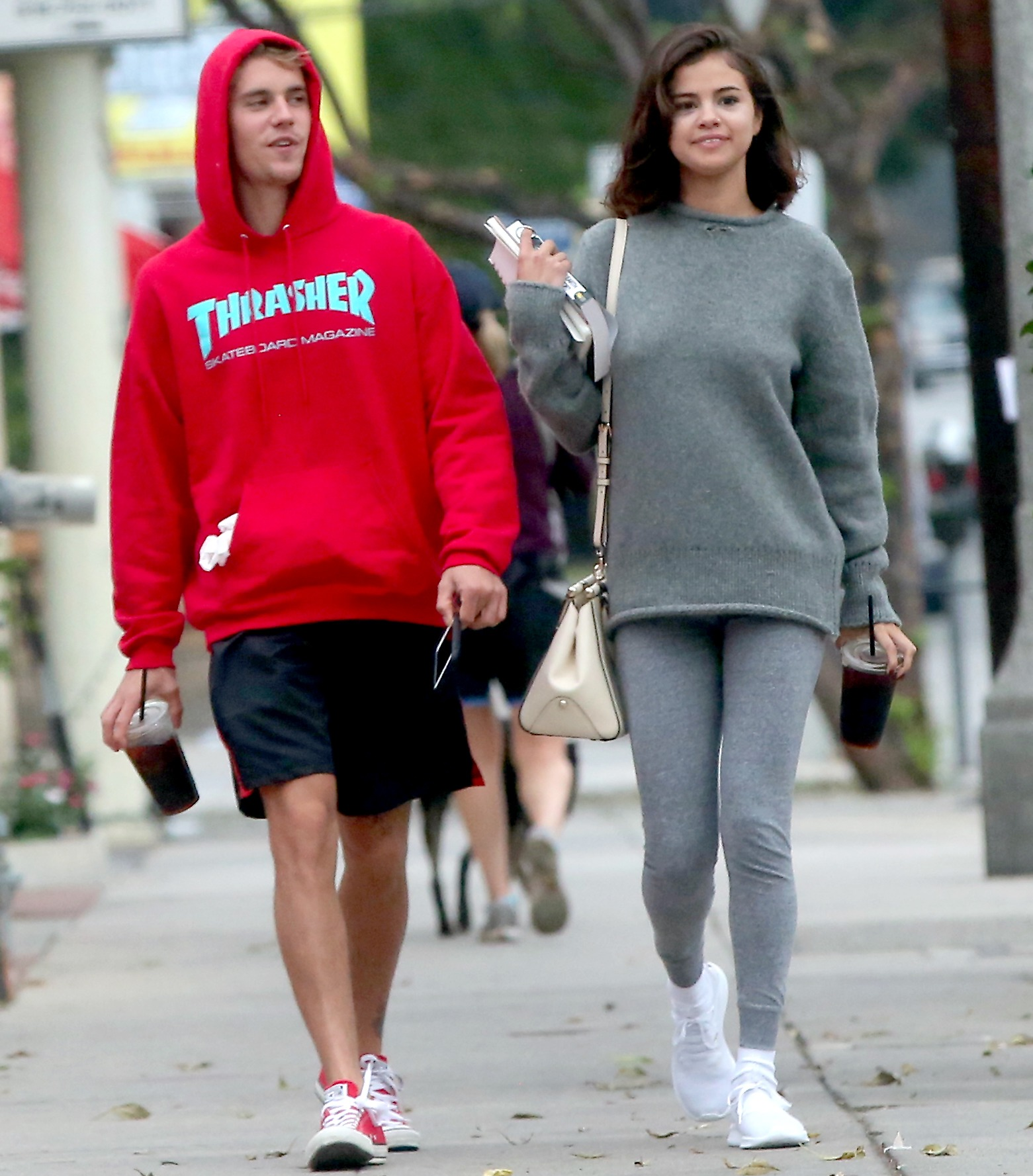 Justin Bieber and Selena Gomez are walking on the street. Justin is wearing a red hoodie and Selena is wearing grey clothes.