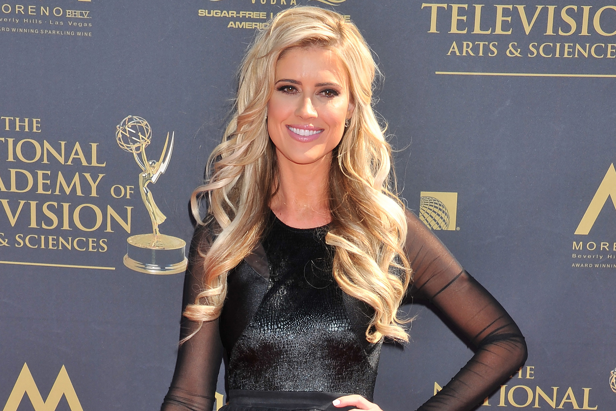 Christina El Moussa wearing a black dress and smiling at a Emmy Awards