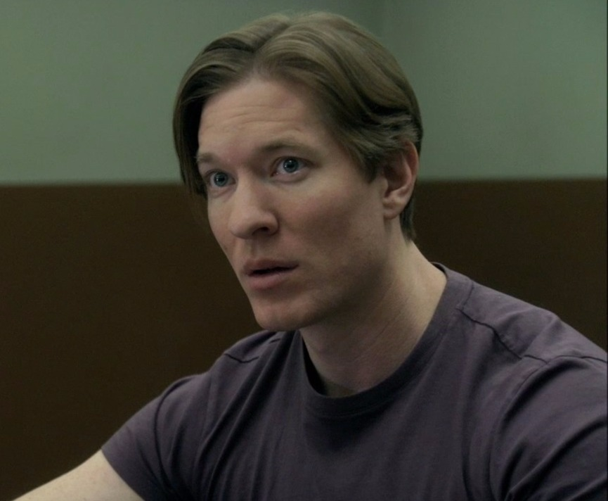 Roger from movie Gacy, Joseph Sikora with his mouth open looks to the side