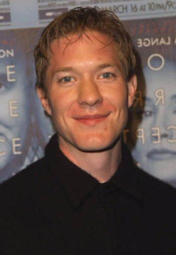 Joseph Sikora with medium sized hair smiles to the camera for a picture