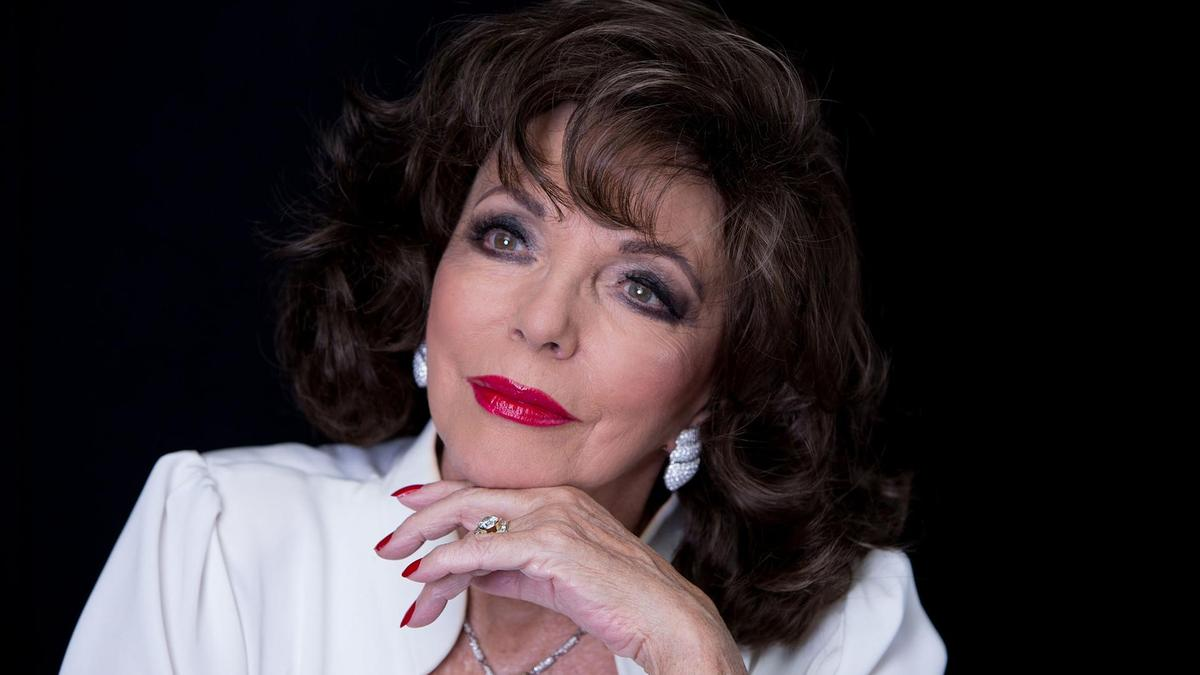 Joan Collins holding her head by putting her hand on her chin