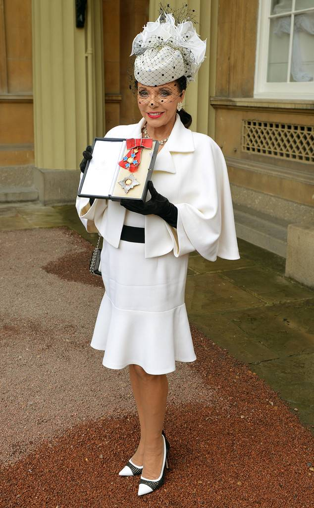 joan holding the honorary medal of dame wearing royal clothes