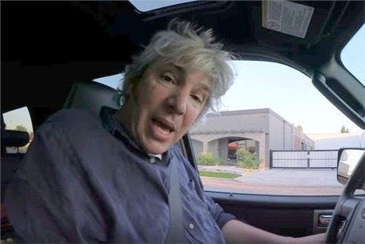 Edd China is taking a video of answering his fan's questions. He is facing the camera and trying to speak. He is in the driver's seat of his car.