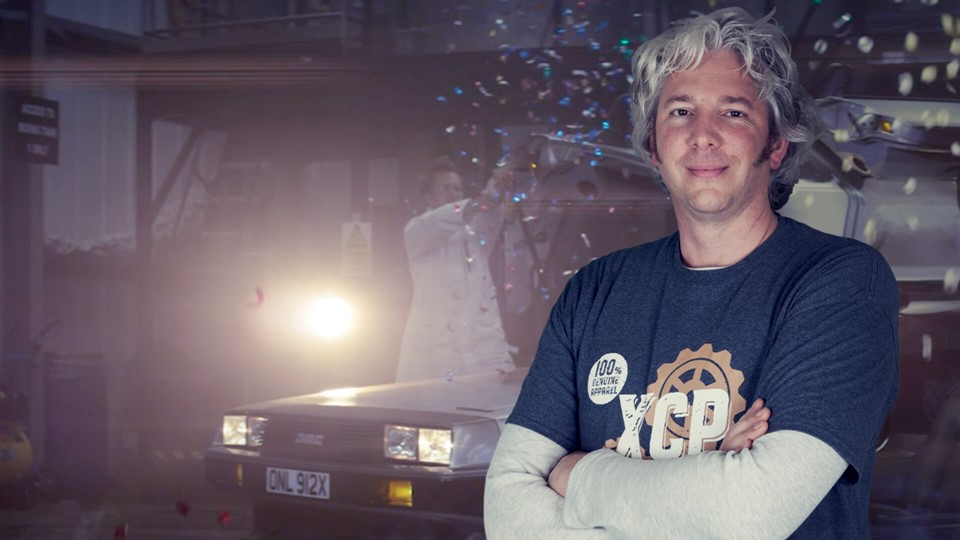 Edd China is wearing blue and grey t-shirt and has a  little smile on his face. He is posing with his hands fold and has a car in the background