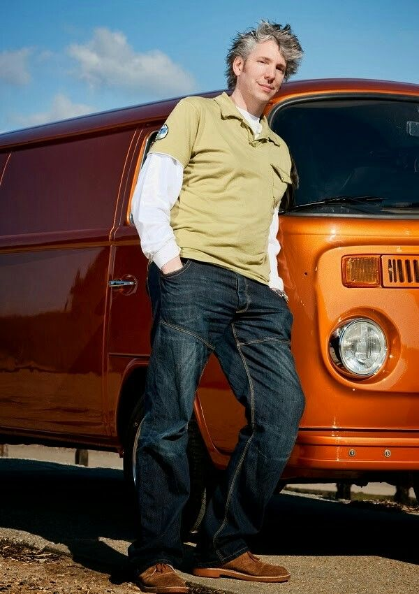 Edd China leaning on a mini van.