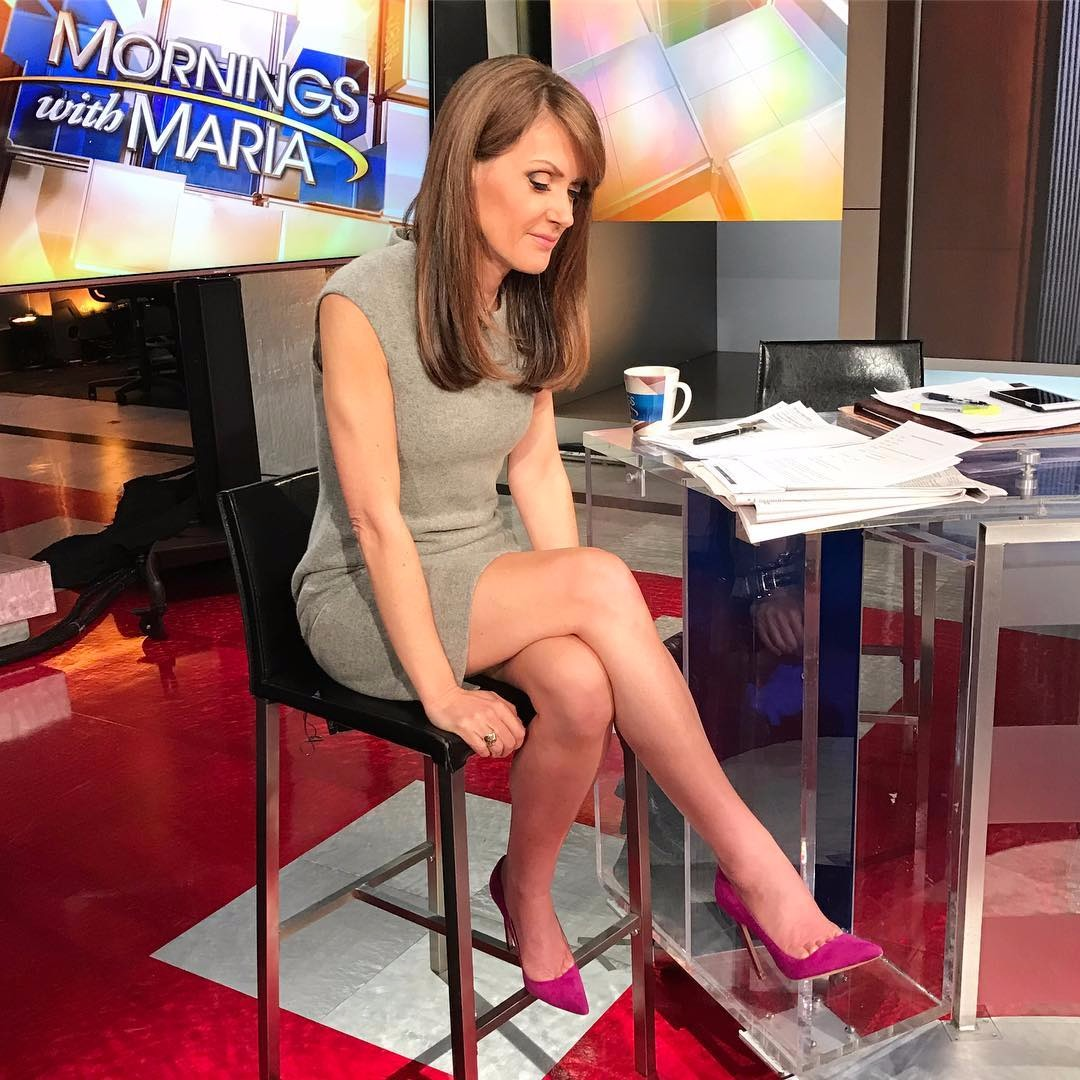 Dagen McDowell looking at her new pair of heels that suits her feet perfectly. She shows off her long and sexy legs through her grey colored dress. She is in the sets of Fox News' Morning with Maria.