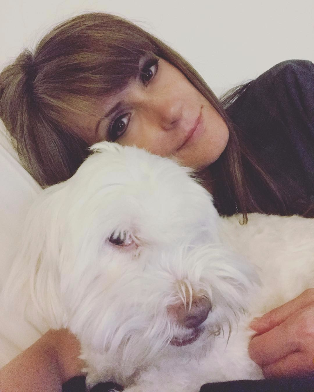 Dagen McDowell relaxing in her bed with her rescue dog. She seems to be in a lazy mood.