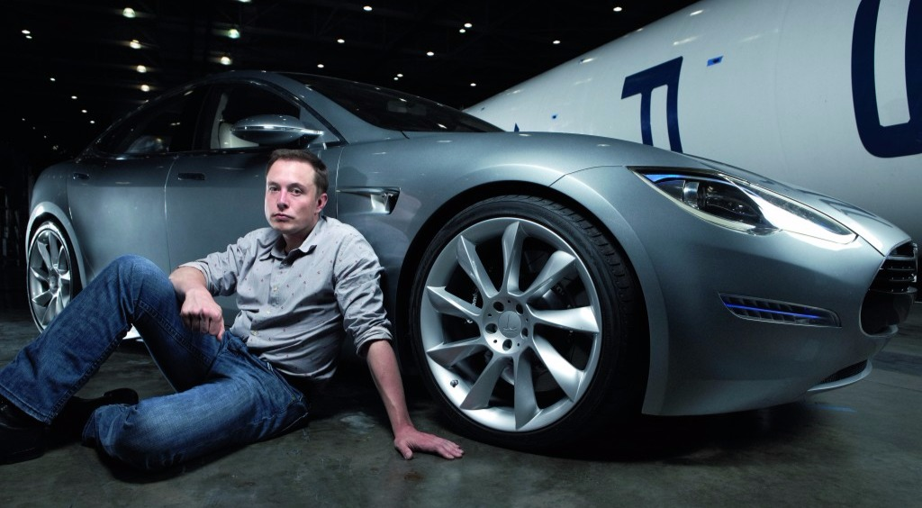 Tesla Motors CEO, Elon Musk's seated pose alongside Tesla Model S in 2012. The car was awarded 'Car of the Year 2013'.