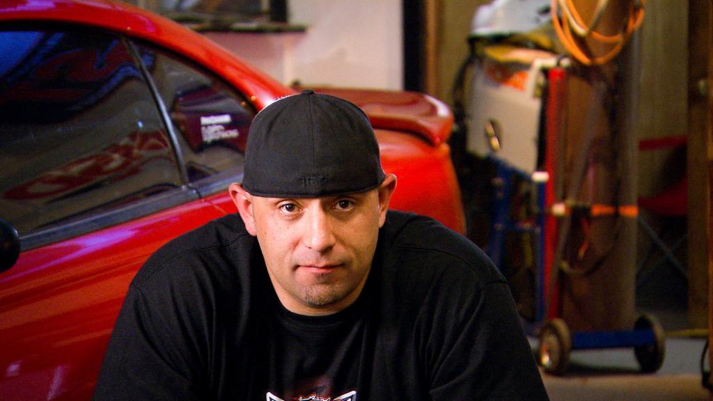 Justin Shearer wearing a cap and a black t-shirt