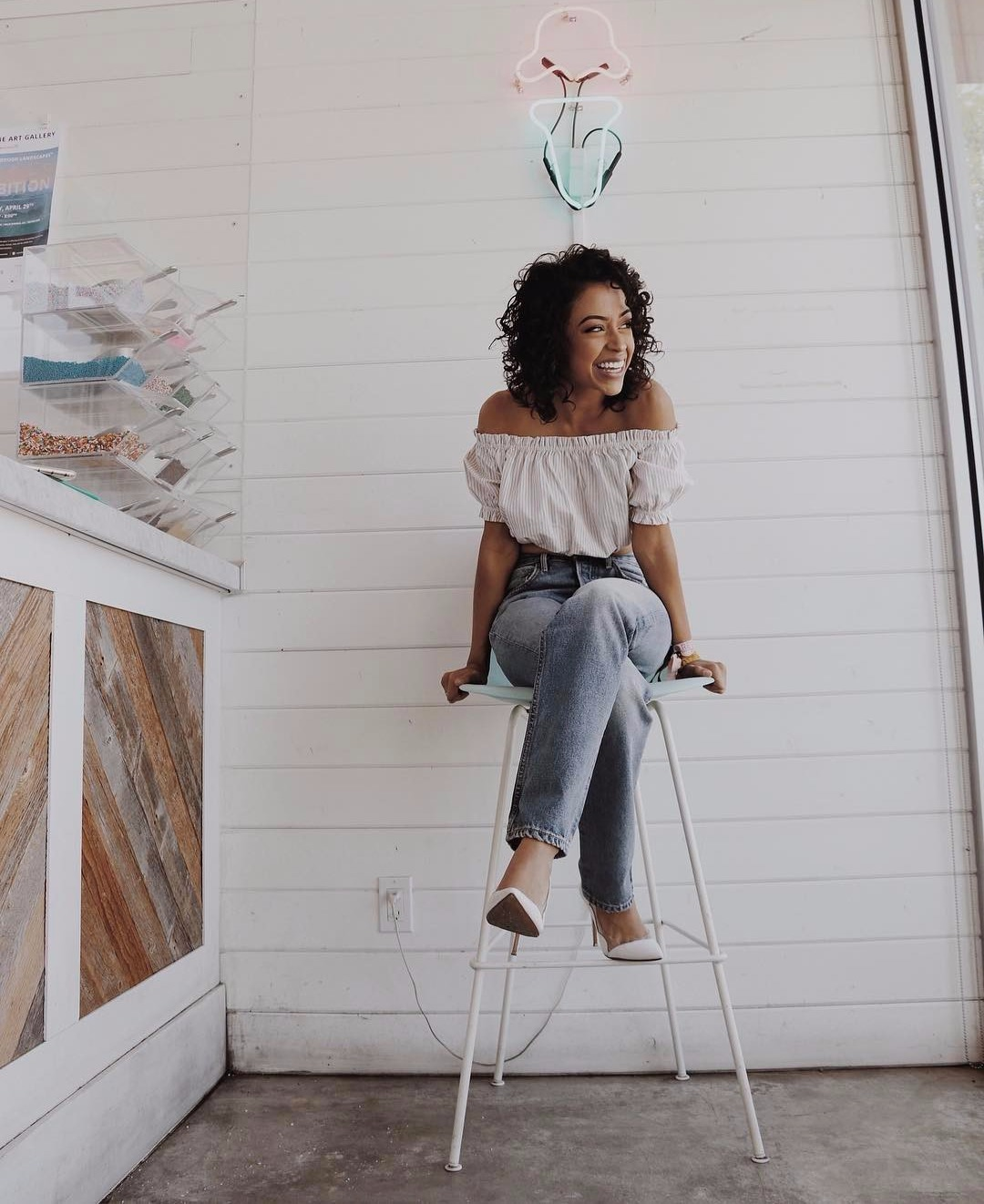 Liza Koshy sitting on a bar stool, there's a neon light above her head