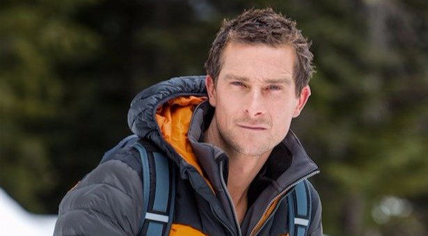 Bear Grylls is looking sporty in his warm grey and orange jacket. He is in a snowy surrounding.