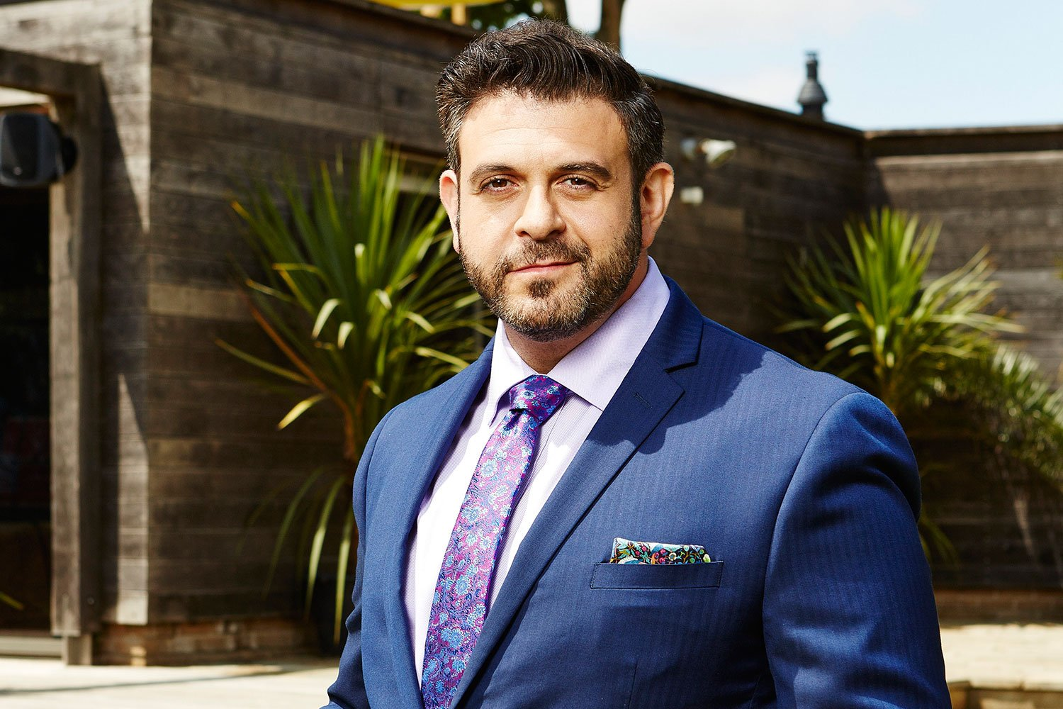 Adam Richman smiling fir for a picture wearing a blue suit