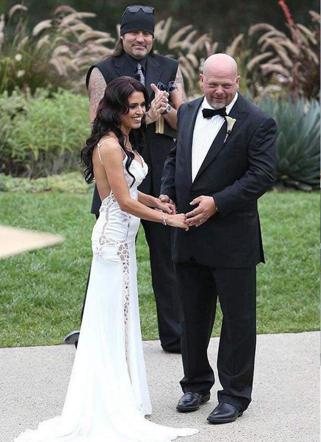 Rick Harrison is standing alongside his wife, Deanna Burditt, on their marriage ceremony. Rick is holding his wife's both hands. Both the couple look dashing in their marriage apparel. Rick is wearing a black suit and a white shirt while Deanna is wearing a stunning white gown.