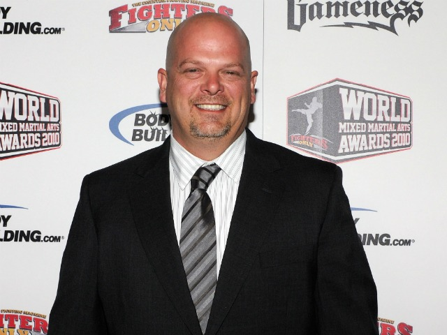Rick Harrison attends an event. He is wearing a white lining shirt and a black suit. His grey tie looks slightly shifted towards the left. Rick faces straight on the camera with a big smile on his face.