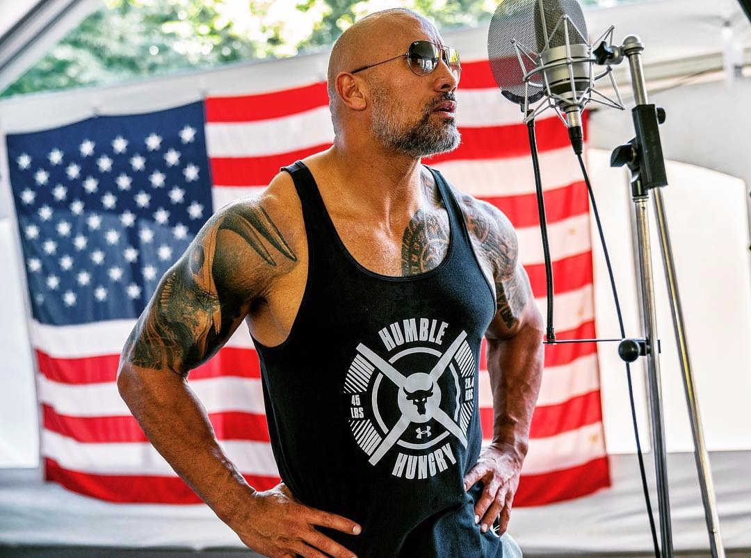The Rock wearing a tank top, there's an American flag behind him and a mic stand next to him