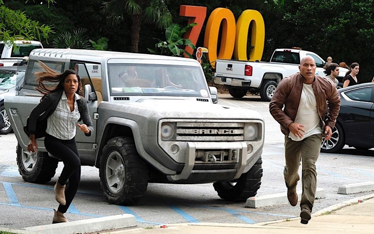 Dwayne Johnson and his co-actor from the movie, Rampage running on the movie set. Ford Bronco 2020 is at the parking behind the actors