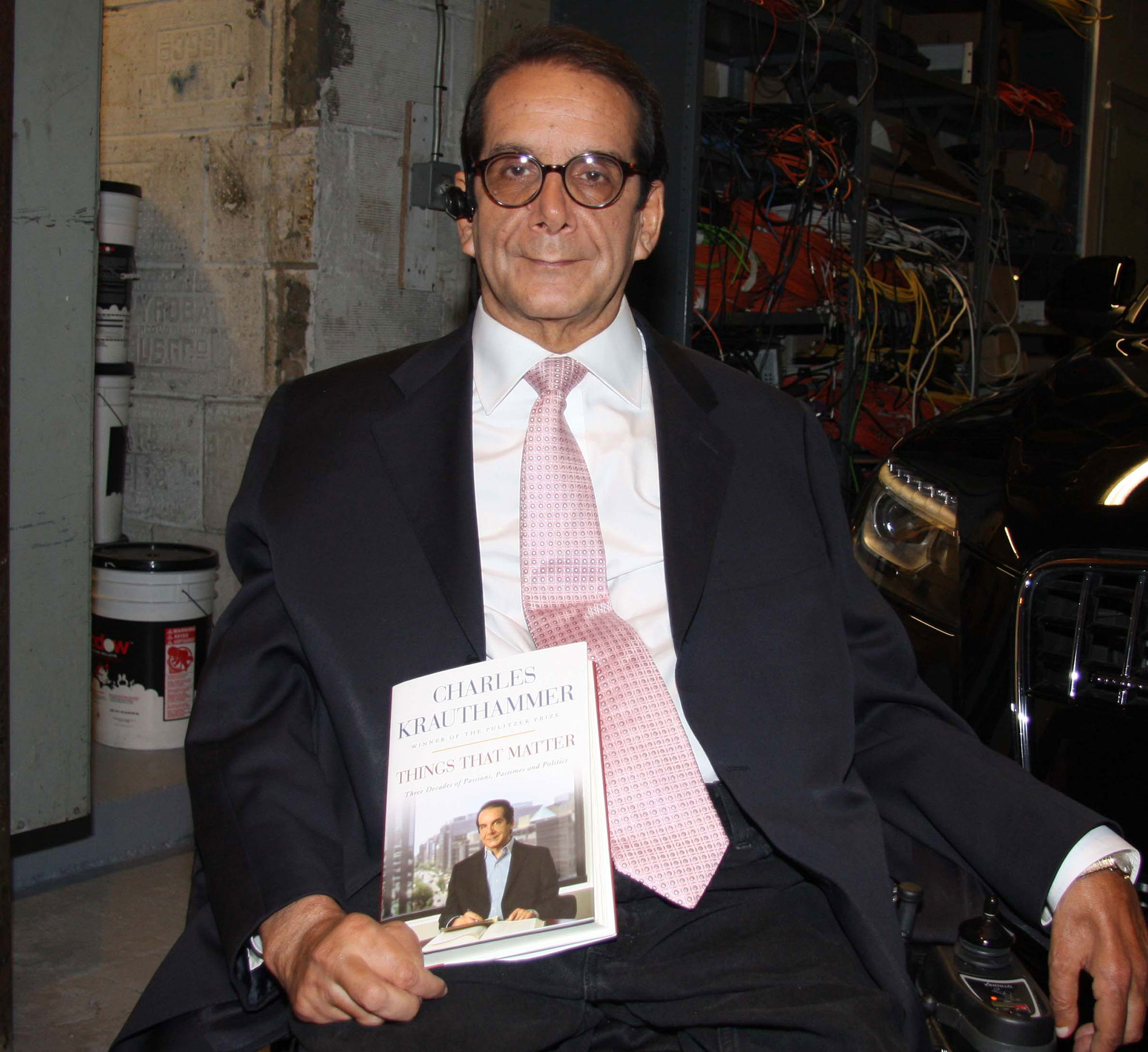 Charles Krauthammer  is sitting with a book on his hand