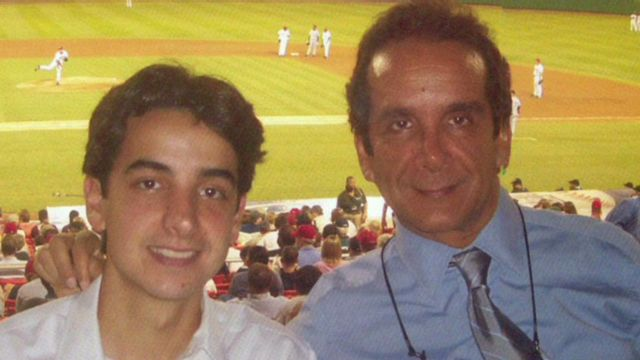Charles Krauthammer with his son Daniel Krauthammer. They are at a stadium. In the background, baseball match is going on.