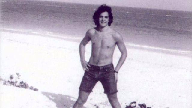 An old black and white image of Charles Krauthammer before his accident. He is shirtless and is standing in the beach.