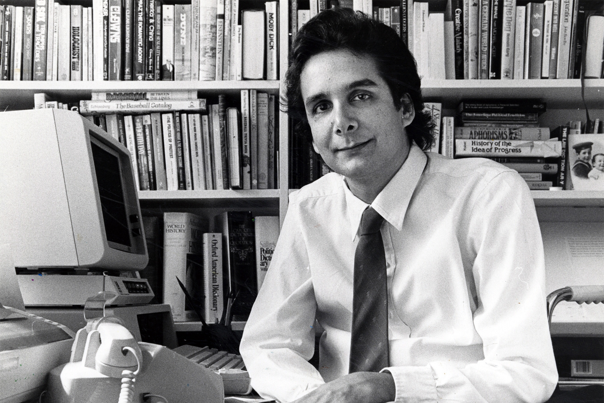 Black and white picture of Charles Krauthammer in front of a old computer
