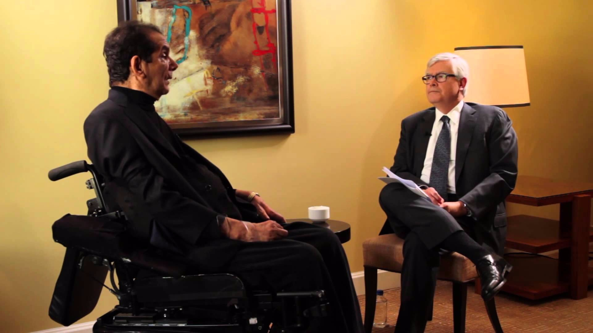 Charles Krauthammer and professor Charles R. Kesler are sitting face to face for an interview. Kesler is sitting on a chair while Charles Krauthammer is sitting in a wheelchair.