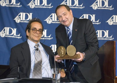 Charles Krauthammer is sitting on a chair and lawyer Abraham H, Foxman is presenting Krauthammer with an award.
