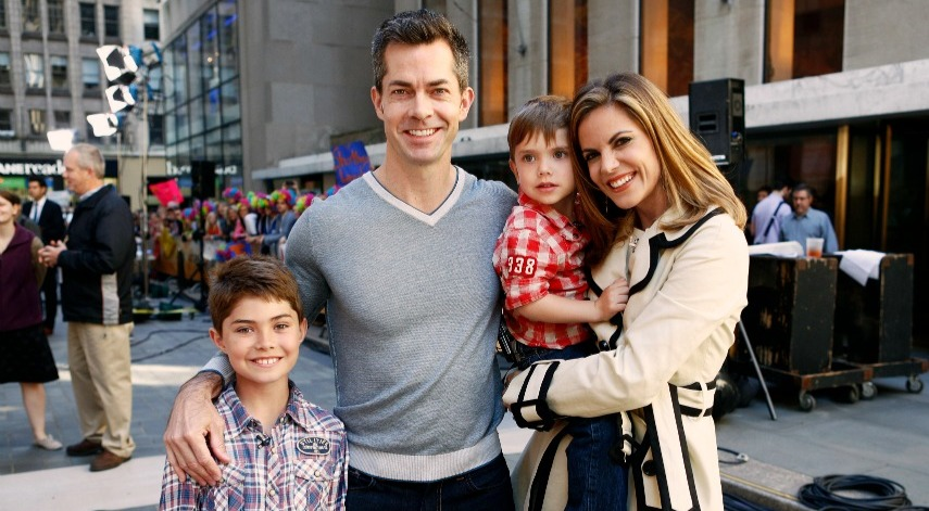 Natalie Morales holding her son while standing next to husband and another son