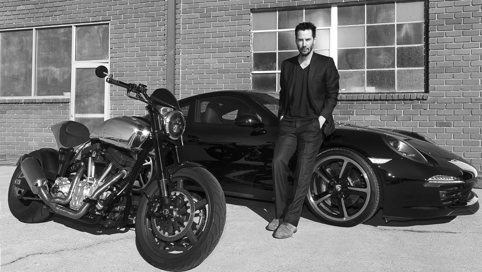 A black and white picture of Keanu beside his Porsche sports car and his custom motorbike
