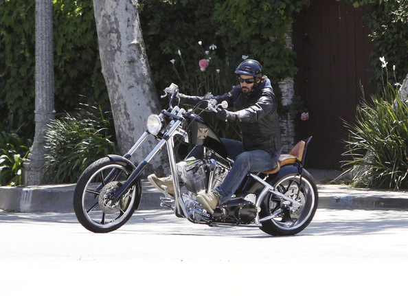 Keanu on his custom motorbike, enjoying a casual ride. He is wearing a leather jacket and jeans