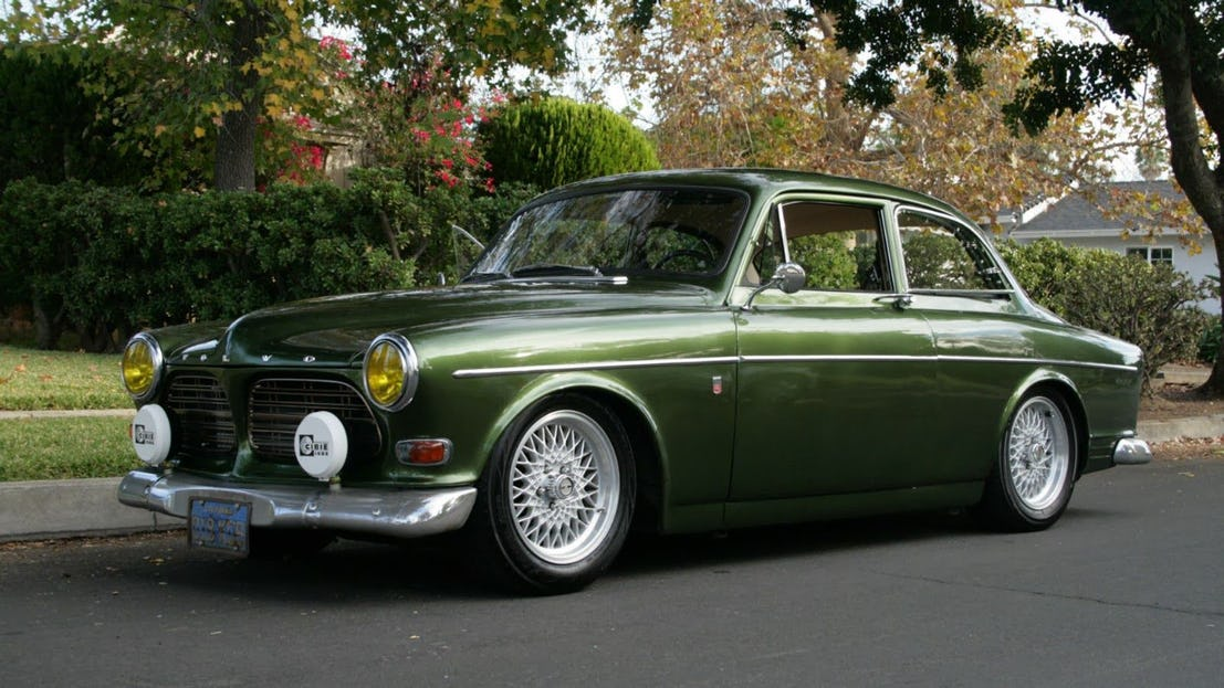A Volvo 122 car of green color. It has yellow headlights and a deep green color