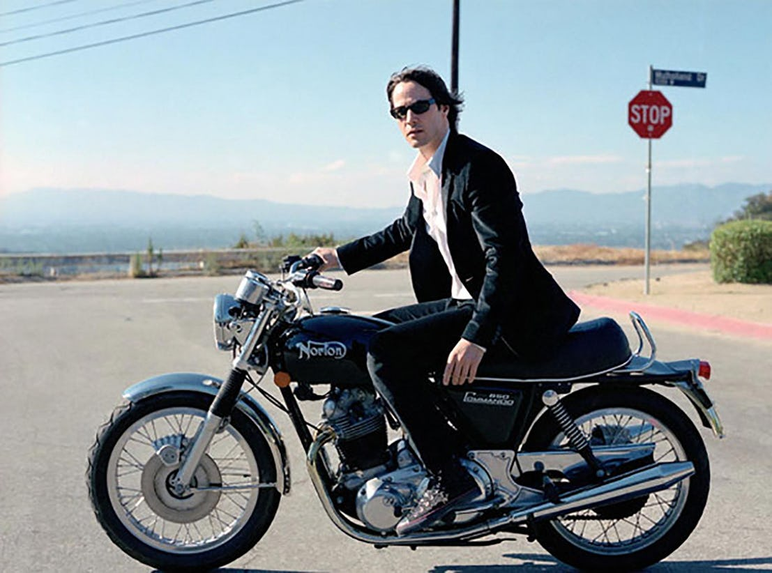 Keanu on is Norton Commando motorbike, he is posing on a road, he is wearing a suit