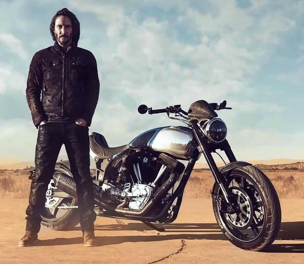 Keanu on a promotional still of his company's motorbike. He is on a desert in full biker gear, a silver KRGT-1 bike besides him