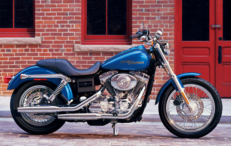 An image of the Harley Davidson Dyna Wide motorbike. The bike has a distinct chopper body and blue paint