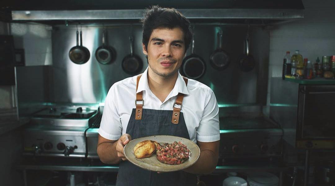 Erwan Heussaff holding a plate in a kitchen
