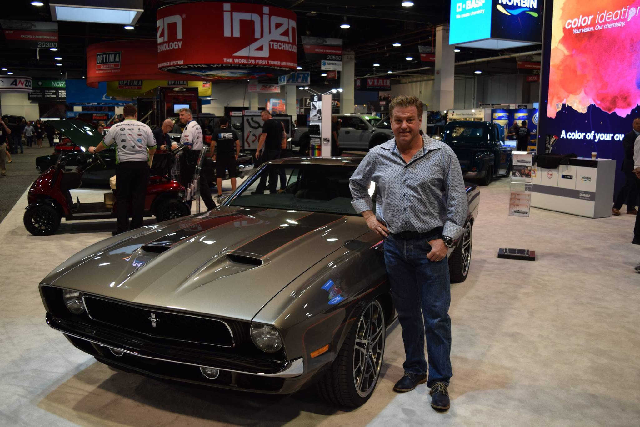 Chip Foose posing in front of a car