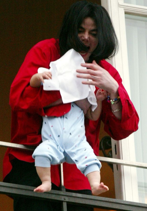 Michael Jackson is carrying his son. He is about to drop him from the balcony.