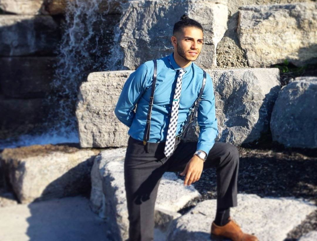 Mena Massoud with his hand resting on his knee, he has a man bun and is wearing pants with suspenders
