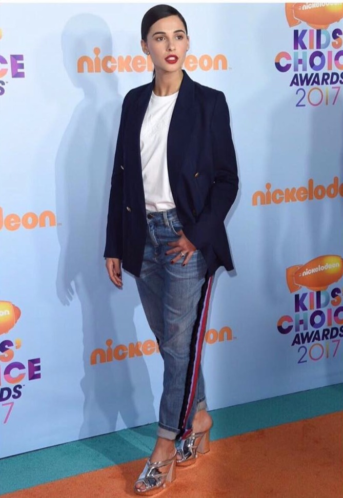 Naomi Scott standing, she has her thumb tucked in her jeans pocket, she's wearing a blazer over a shirt