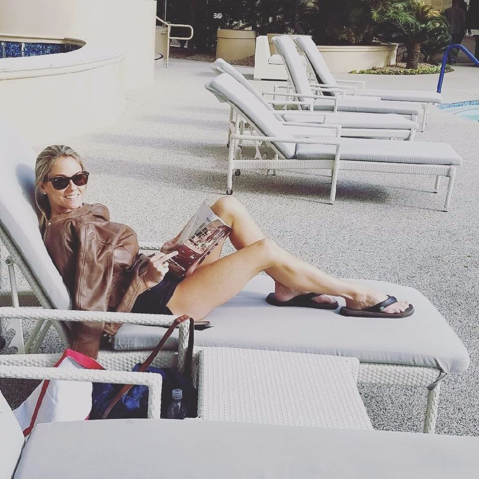 Nicole Curtis relaxing in a sunbathing chair. She is wearing a bikini but has covered her upper body part with her brown jacket. She is reading a magazine.