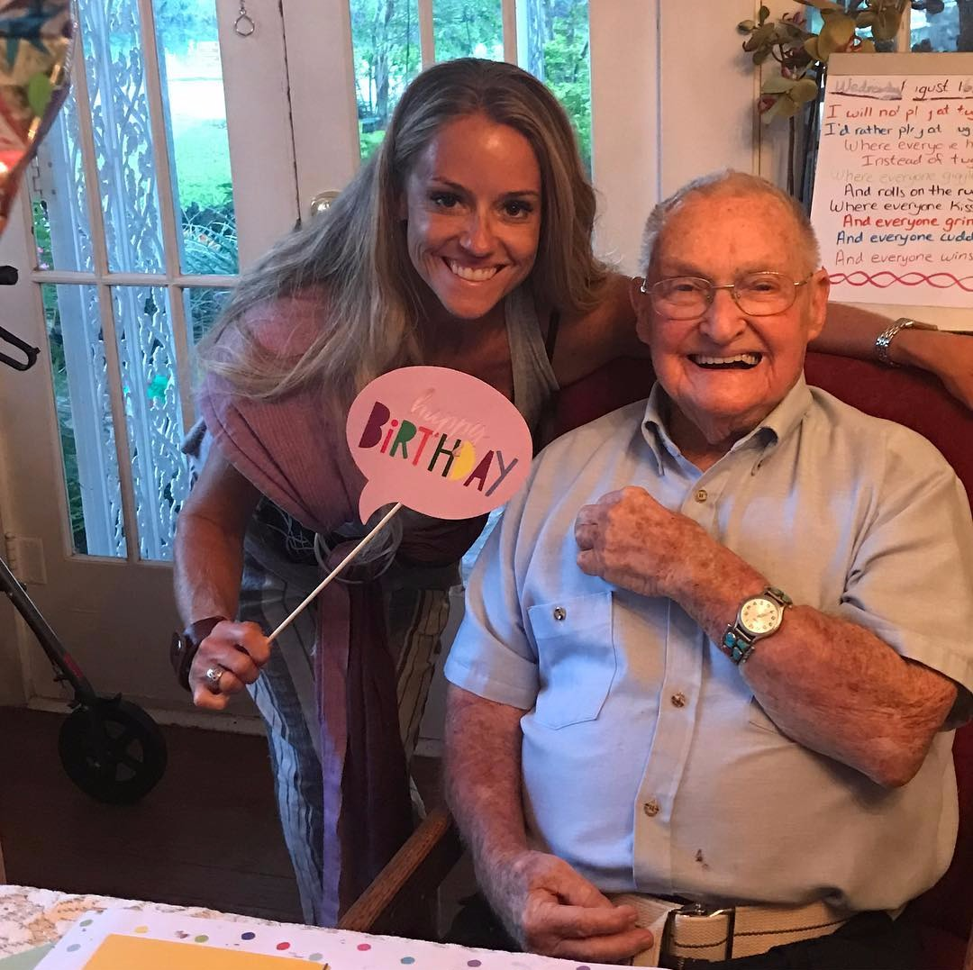 """Nicole Curtis is standing close to a chair where her grandfather is sitting. She is holding a card which says """"happy birthday."""""""
