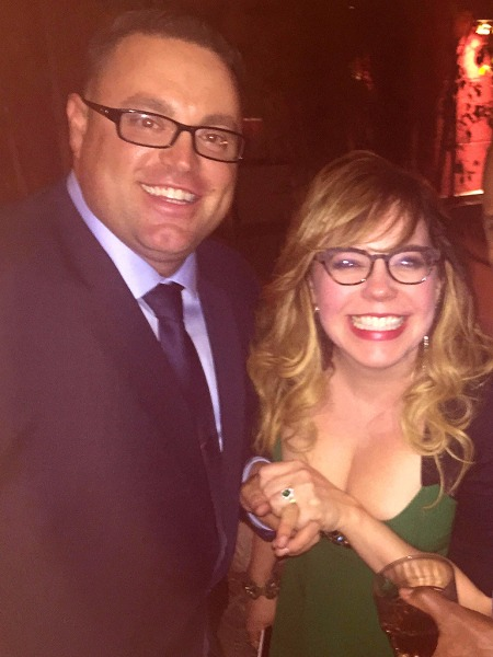 Kirsten Vangsness and Keith Hanson holding hands, the happy couple share a big smile to the camera