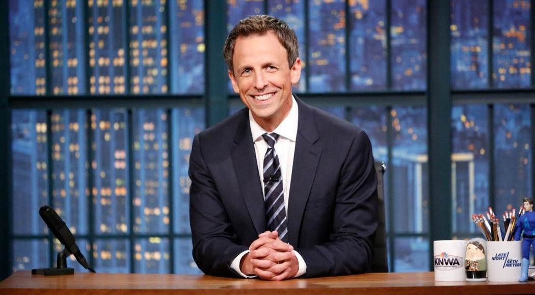 Seth Meyers in the studio set of Late Night. He wears a smile and a dashing black suit as he poses for the camera.