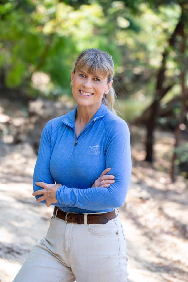 Terri Irwin smiling for a picture wearing a blue zip shirt and safari pants