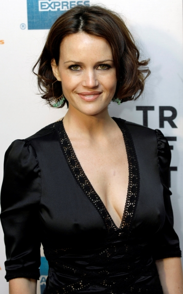 Carla Gugino looks hot in the black dress. She is facing the camera with a subtle smile on her face.