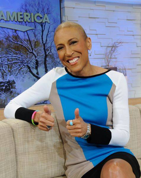 Robin Roberts sitting on a couch in a bald head