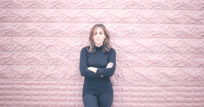 News Correspondent Hallie Jackson folding her arms and leaning on the big wall. She is staring at the camera in her black outfit