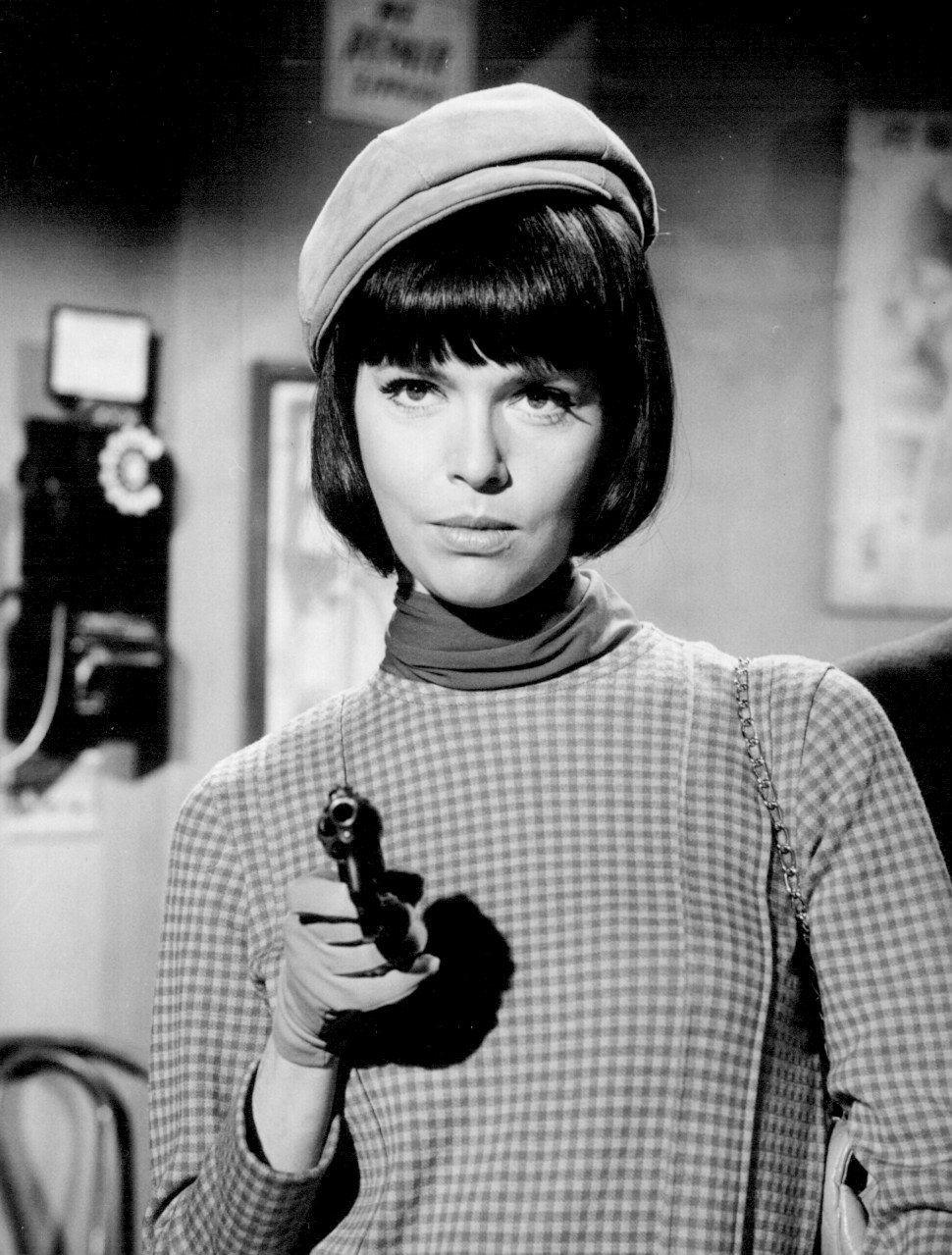 Barbara Feldon in the role of Agent 99. She is pointing gun towards someone. The picture is B&W.