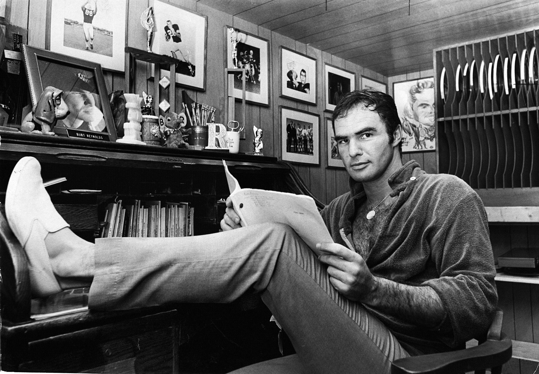 Burt Reynolds holding a paper in his hands while sitting on a chair