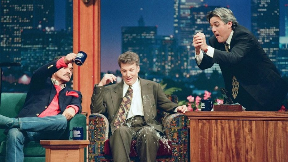 Burt Reynolds pouring water on Marc Summers while sitting on a couch and Jay Leno is standing on the set of The Tonight Show with Jay Leno