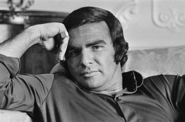 Young Burt Reynolds sitting on a couch